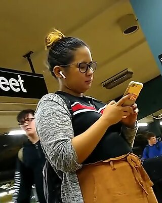 Cute chubby Filipina girl with glasses waiting for train
